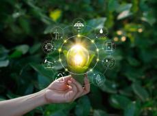Hand met gloeilamp en pictogrammen; energiebronnen voor hernieuwbare en duurzame ontwikkeling