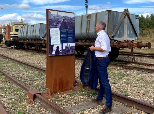 Minister Diependaele leest een infobord bij de oude treinstellen in B-Mine in Beringen